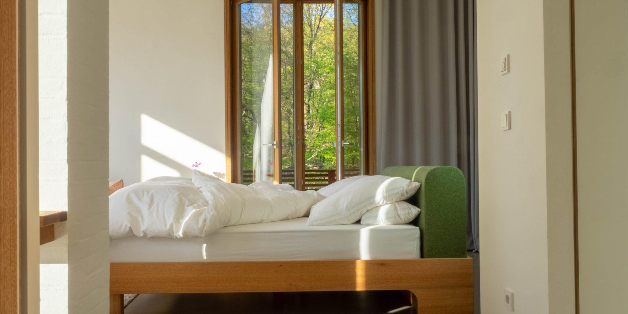 bel étage - Park: Blick durch die Verbindungstür zwischen beiden Wohnungen auf das Bett an der Parkseite. Ein identisches Doppelbett steht in der bel étage Allee